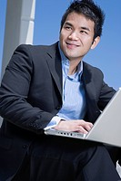 Asian businessman working on laptop outdoors