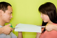Close_up of a young man and a young woman cutting a paper with scissors