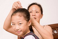 Mother adjusting her daughter´s hair with a hair clip
