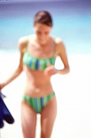 Blurred photo of a young woman in a bikini at the beach