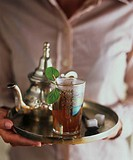 Hands holding tray of mint tea