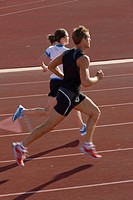 Two athletes running on track
