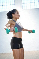 Woman exercising with hand weights in gym