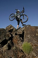Cyclist carrying mountain bike on rocks