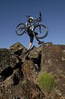 Cyclist carrying mountain bike on rocks