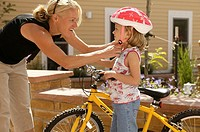 Mother adjusting cycling helmet on daughter's 6_7 head
