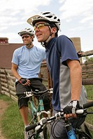 Two male cyclists resting n rural landscape