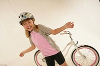 Studio portrait of girl 6_7 with arms outstretched in front of bicycle