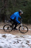 Man riding mountain bike on trail