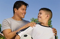Boy 13_15 holding soccer ball with young man