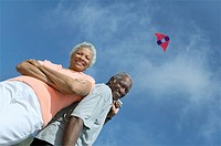 Senior couple flying kite outdoors low angle view portrait