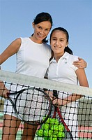 Mother and daughter standing at net on tennis court portrait low angle view