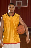 Basketball player with ball on indoor court portrait