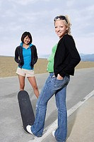 Two young female skateboarders on road