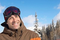 Young man wearing ski goggles on head in snow portrait.