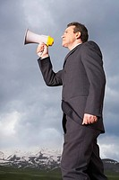 Businessman in mountain field Speaking Through Megaphone low angle view