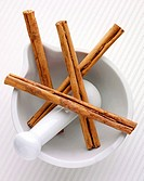 Four cinnamon sticks in a mortar with pestle
