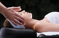 Side profile of a young woman getting massage from a massage therapist