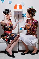 Two young women sitting in a hair salon and looking at each other