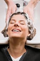 Young woman getting hair shampooed at the hair salon