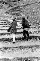 Rear view of a boy with his sister moving up on steps