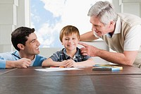 Portrait of a boy doing homework with the help of his father and grandfather