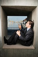 Side profile of a businessman sitting on a window sill and operating a mobile phone