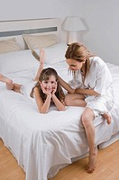 High angle view of a mid adult woman sitting on the bed with her daughter