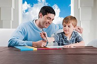 Mid adult man assisting his son in his homework