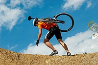 Low angle view of a young man carrying a mountain bike on his shoulders