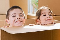 Close_up of a boy and a girl smiling in a cardboard box