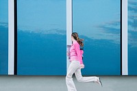 Side profile of a businesswoman running in the corridor of an office