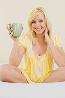 Portrait of a young woman sitting on the bed and holding a cup of tea