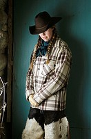 A cowgirl deep in thought, leaning against the cabin wall