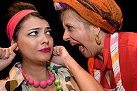 Close_up of a mature woman shouting and her daughter sticking fingers in her ears