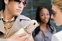 Close_up of a young man holding a puppy and a young woman looking at him