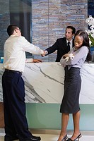Young man shaking hands with a receptionist and a young woman holding a puppy