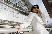 Low angle view of a businesswoman talking on a mobile phone outside an airport