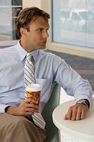 Businessman holding a coffee cup and thinking