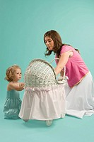 Mid adult woman looking at a baby carriage with her daughter