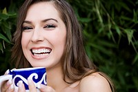 Portrait of a young woman holding a tea cup and smiling