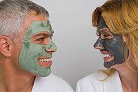 Close_up of a mature couple wearing facial masks and smiling