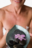 Close_up of a mature woman holding a bowl of pebbles and a flower