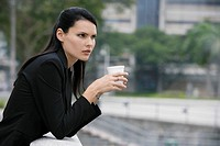 Side profile of a businesswoman holding a disposable cup and thinking