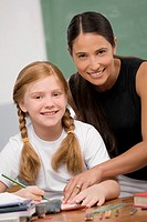 Portrait of a female teacher teaching a schoolgirl in a classroom