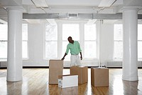 Man unpacking boxes in empty office