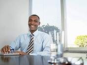Businessman laughing by table portrait