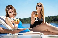 Women having drinks on lounge chairs