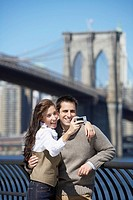 Couple taking photograph with Brooklyn Bridge in background, New York City, New York, USA