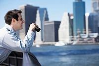 Man using binoculars, Manhattan in background, New York City, New York, USA